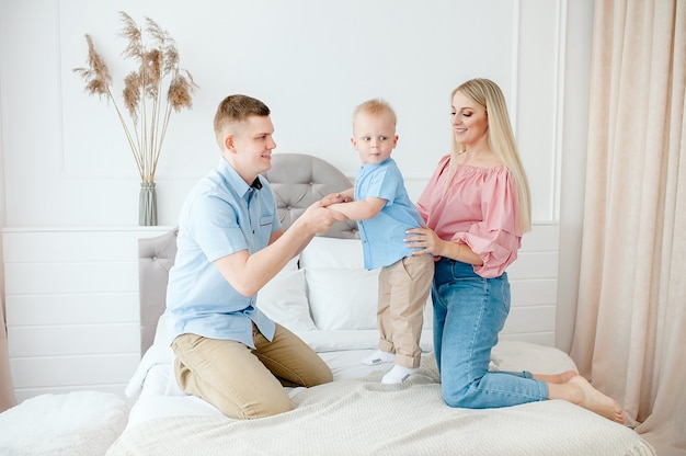 Famiglia felice con un bambino carino. mamma, papà, figlio stanno giocando sul letto in una stanza luminosa e accogliente di casa.