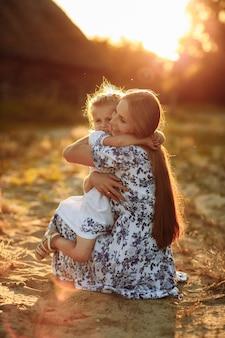 Famiglia felice. concetto di festa della mamma. generi il gioco con la sua piccola ragazza della figlia del bambino il giorno di estate del sole. bella luce al tramonto nel parco.