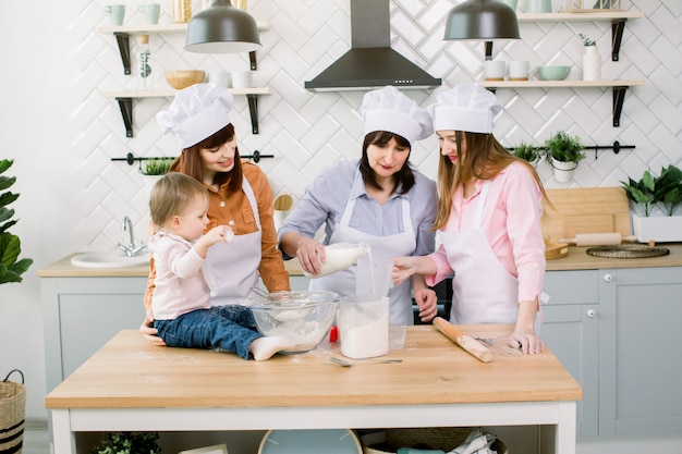 Famiglia felice cottura in cucina. nonna con le figlie e la nipote che preparano l'impasto, la nonna versa il latte da una bottiglia in un misurino