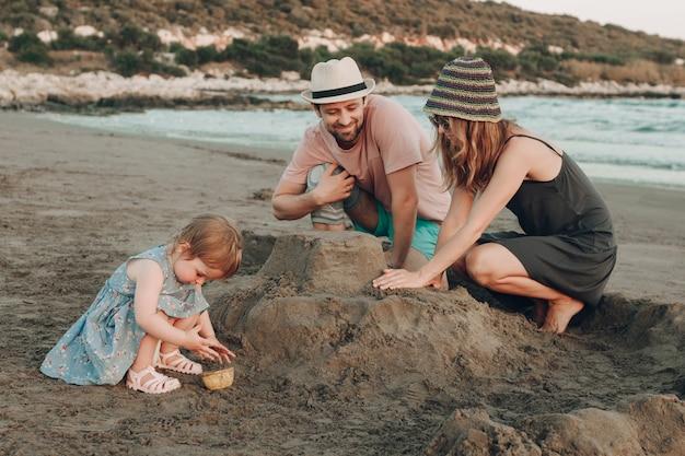 Famiglia felice dei pantaloni a vita bassa alla spiaggia che costruisce il castello della sabbia