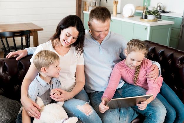 Famiglia felice dell'angolo alto con il dispositivo