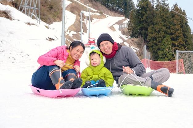 Famiglia felice divertendosi all'aperto, padre asiatico della madre e figlio sveglio del ragazzo del bambino che giocano nella neve