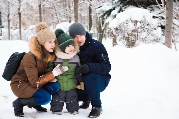 Famiglia felice divertendosi e giocando con la neve nella foresta