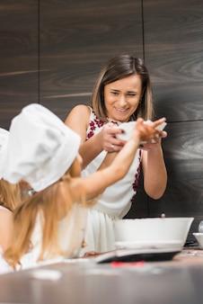 Famiglia felice divertendosi in cucina mentre si prepara il cibo
