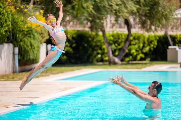 Famiglia felice divertirsi insieme nella piscina all'aperto