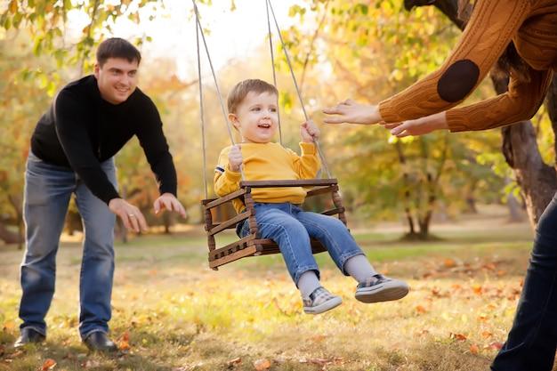 Famiglia felice divertirsi su un giro in altalena in un giardino un giorno d'autunno
