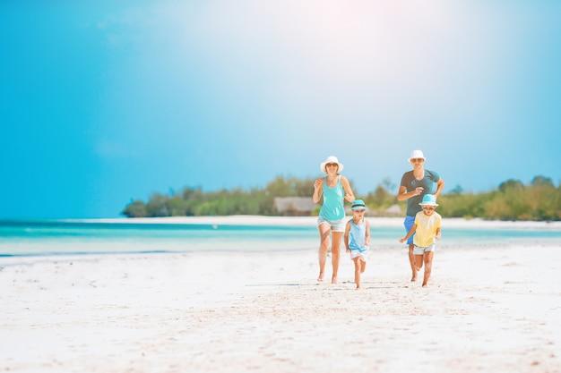 Famiglia felice divertirsi su una spiaggia tropicale