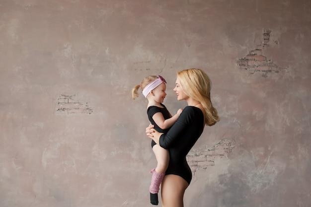 Famiglia felice, due ballerine, madre e figlia in body ginnico nero contro il muro rosa