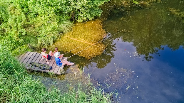 Famiglia felice ed amici che pescano insieme all'aperto vicino al lago di estate, vista superiore aerea da sopra