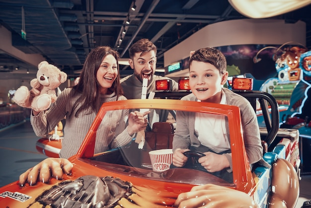 Famiglia felice, figlio che guida l'automobile del giocattolo in parco di divertimenti