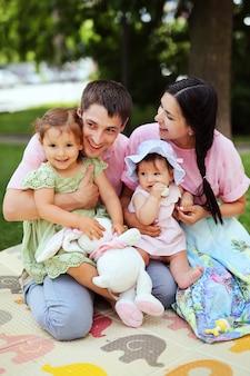 Famiglia felice. genitori sorridenti con bambini. uomo bello e bella donna con le piccole figlie divertirsi nel parco estivo.