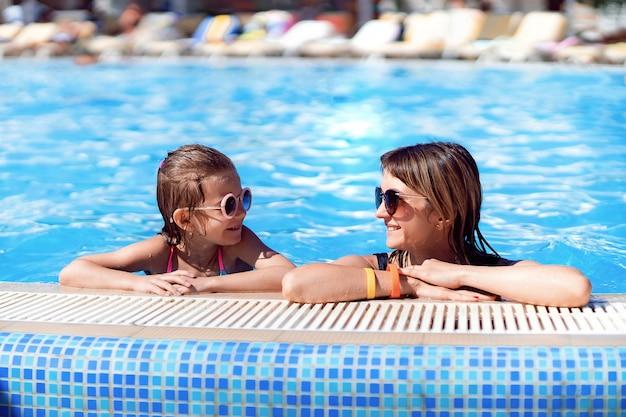 Famiglia felice, giovane madre attiva e adorabile piccola figlia divertirsi in una piscina godendo le vacanze estive in un resort tropicale