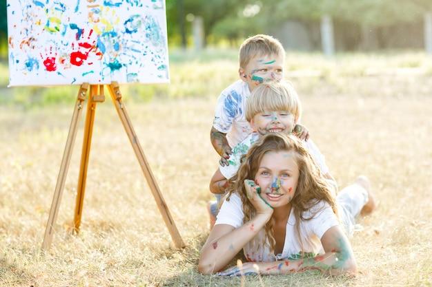 Famiglia felice. giovane madre graziosa divertendosi con i suoi bambini all'aperto. pittura di famiglia