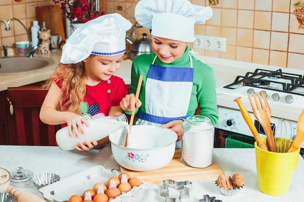 Famiglia felice i bambini divertenti stanno preparando l'impasto, cuociono i biscotti in cucina