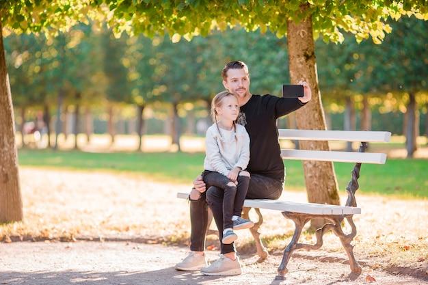 Famiglia felice in autunno. padre e bambino si divertono a prendere selfie in bella giornata d'autunno