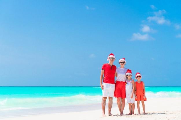 Famiglia felice in cappelli di babbo natale durante le vacanze di natale tropicale