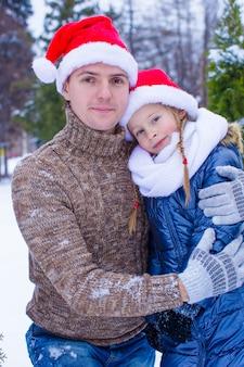 Famiglia felice in cappelli di santa con l'albero di natale all'aperto