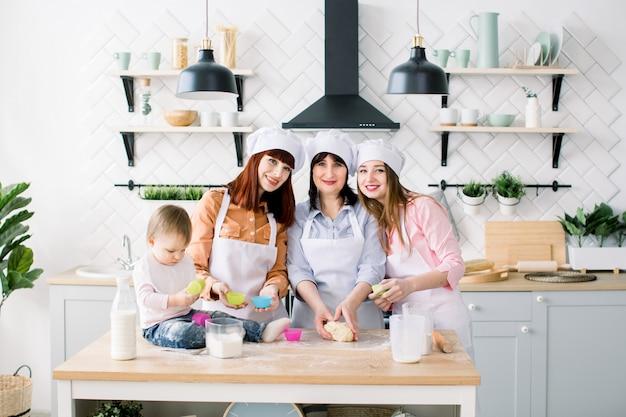 Famiglia felice in cucina. giovane donna e sua sorella, donna di mezza età e piccola figlia carina cucinare cupcakes per la festa della mamma, serie di foto di lifestyle casual nella vita reale interiore