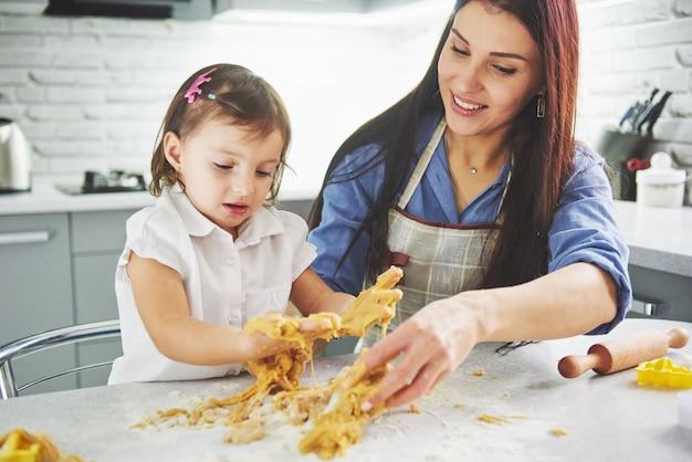 Famiglia felice in cucina. la madre e la figlia che preparano la pasta, cuociono i biscotti.