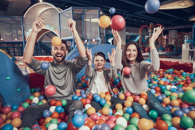 Famiglia felice in piscina con le palle per trascorrere le vacanze insieme.