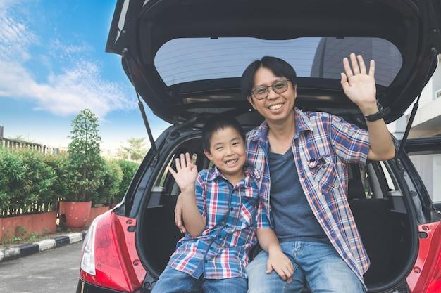 Famiglia felice in viaggio, seduti nel bagagliaio della macchina