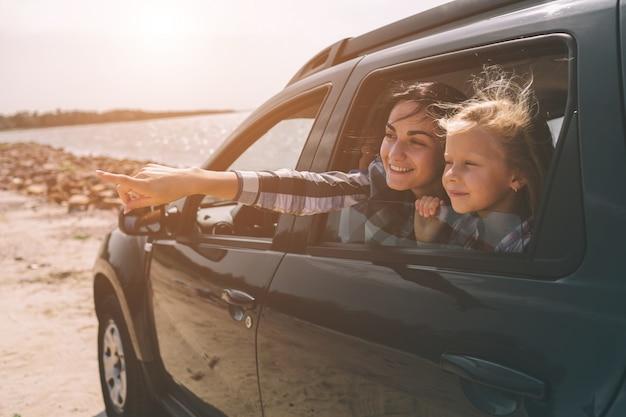 Famiglia felice in viaggio sulla strada. papà, mamma e figlia viaggiano in riva al mare o sull'oceano o sul fiume. giro estivo in automobile