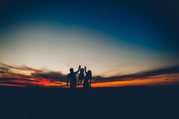 Famiglia felice insieme, genitori con il loro piccolo bambino al tramonto. padre, alzando, bambino, in, aria.