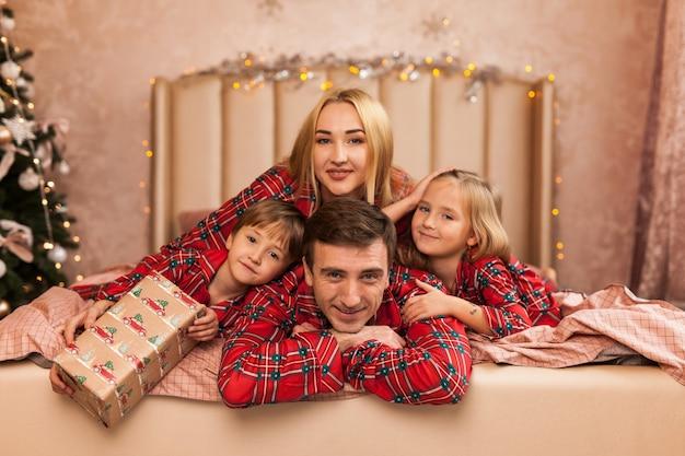 Famiglia felice madre padre e bambini sulla mattina di natale a letto in pigiama