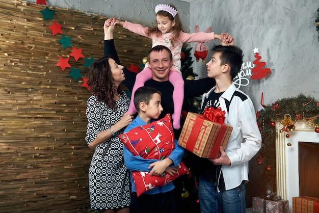 Famiglia felice: mamma, papà e tre figli davanti al camino per le vacanze invernali. vigilia di natale e capodanno.