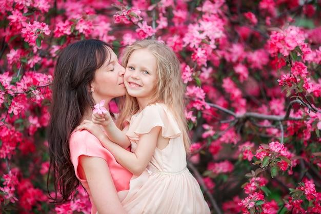 Famiglia felice nel giardino delle mele in fiore in bella giornata di primavera