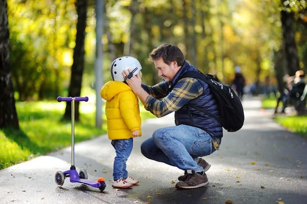 Famiglia felice nel parco d'autunno. padre di mezza età che aiuta il suo piccolo figlio a mettere il suo casco. ragazzo attivo del bambino per guidare uno scooter. sicurezza dei bambini
