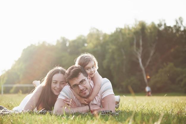 Famiglia felice, padre della madre e figlia del bambino nella natura al tramonto.