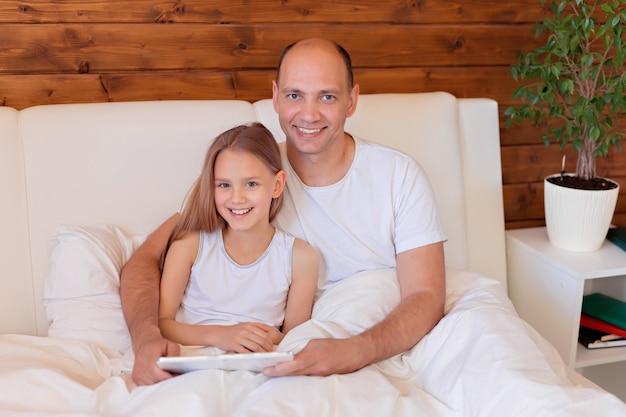 Famiglia felice, papà e figlia che parlano sul tablet a casa a letto. insegnamento a distanza.