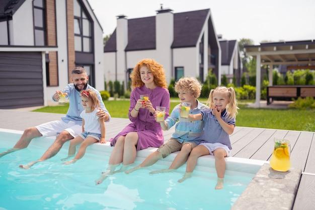 Famiglia felice positiva che si siede vicino alla piscina