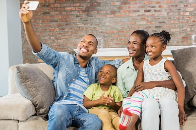 Famiglia felice prendendo un selfie sul divano