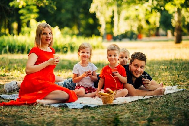 Famiglia felice su una coperta che beve succo