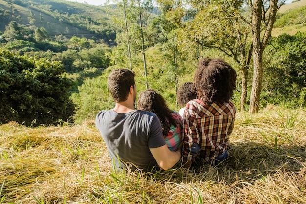 Famiglia felice sulla collina vista da dietro