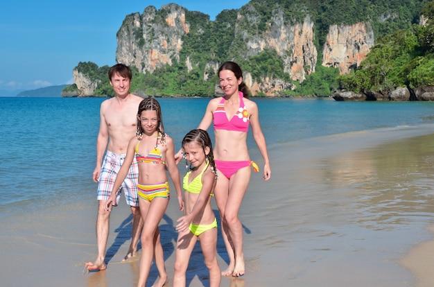 Famiglia felice sulla spiaggia tropicale divertendosi in vacanza
