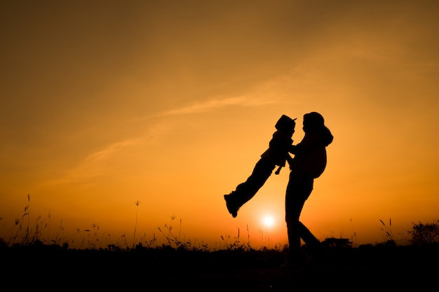 Famiglia felice. una madre e un figlio che giocano nei campi di erba all'aperto alla siluetta di sera