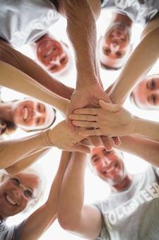 Famiglia felice volontario mettendo le mani insieme