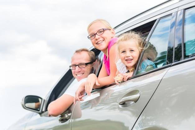 Famiglia guida in auto in vacanza estiva