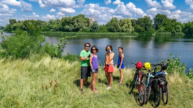 Famiglia in bici all'aperto, genitori attivi e bambini in bicicletta, vista aerea superiore della famiglia felice