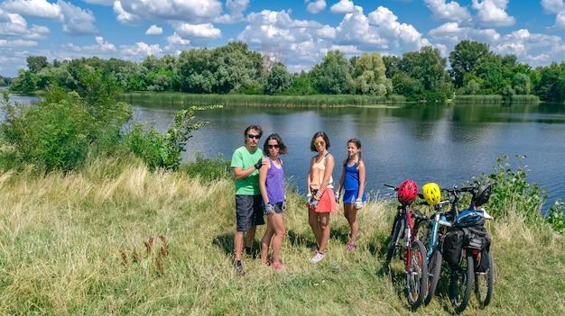 Famiglia in bici in bicicletta all'aperto, genitori attivi e bambini in bicicletta, vista aerea superiore della famiglia felice con bambini che si rilassano vicino al bellissimo fiume dall'alto, concetto di sport e fitness