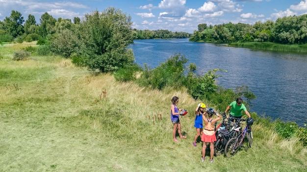 Famiglia in bici in bicicletta all'aperto, genitori attivi e bambini in bicicletta, vista aerea superiore della famiglia felice con bambini che si rilassano vicino