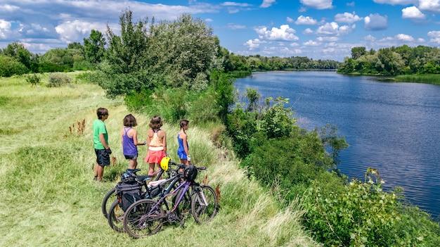 Famiglia in bici in bicicletta all'aperto, genitori e bambini in bicicletta, vista aerea aerea della famiglia felice con i bambini che si rilassano vicino al bellissimo fiume dall'alto, fine settimana e vacanze sport e concetto di fitness