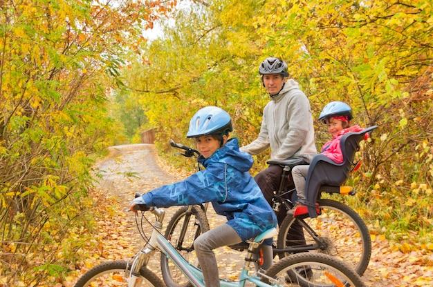 Famiglia in bicicletta all'aperto, autunno d'oro nel parco. padre e figli in bici. sport di famiglia