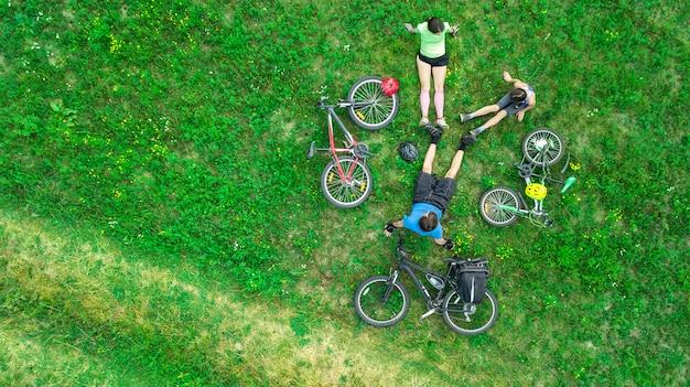 Famiglia in bicicletta in bici all'aperto vista aerea dall'alto, felici genitori attivi con bambino divertirsi e rilassarsi sull'erba, sport di famiglia e fitness durante il fine settimana