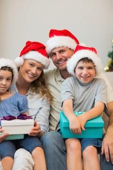 Famiglia in cappello di natale che tiene presenta sul divano