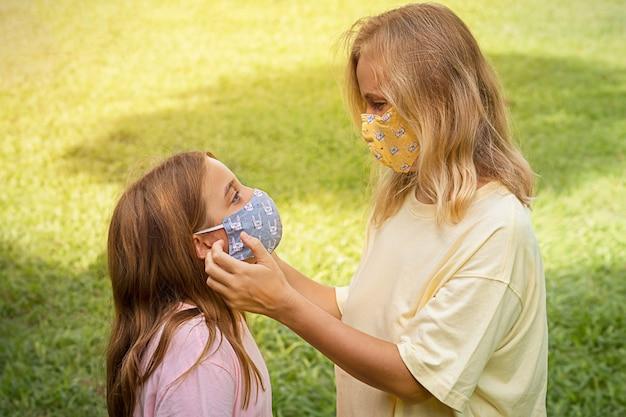 Famiglia in maschera facciale nel parco all'aperto. madre e bambino indossano una maschera per il viso durante il coronavirus e l'epidemia di influenza. protezione da virus e malattie