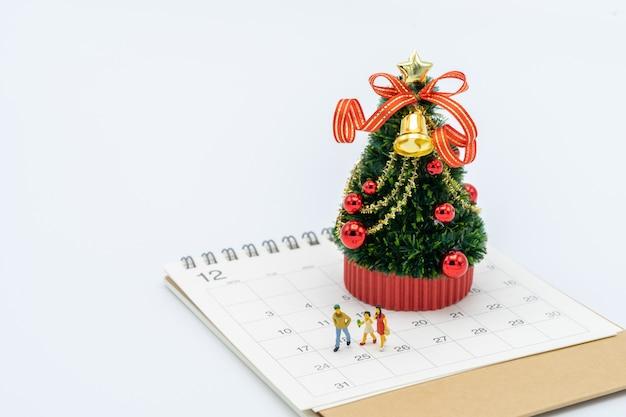 Famiglia in miniatura 3 persone in piedi sull'albero di natale festeggia il natale